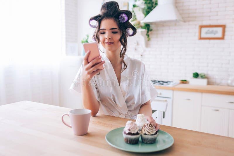 镇静平安的年轻女人看看电话在手中 杯饮料用在板材的薄煎饼在桌上 单独在厨房里 库存图片