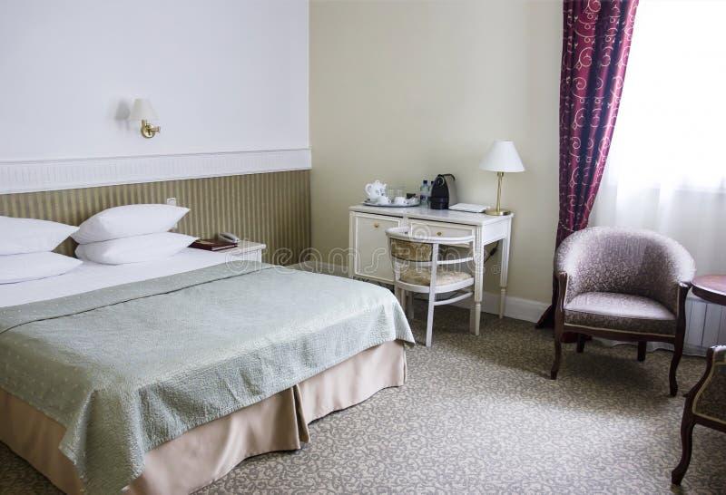 镇静棕色口气、减速火箭的样式、床、书桌和扶手椅子的旅馆客房 库存图片