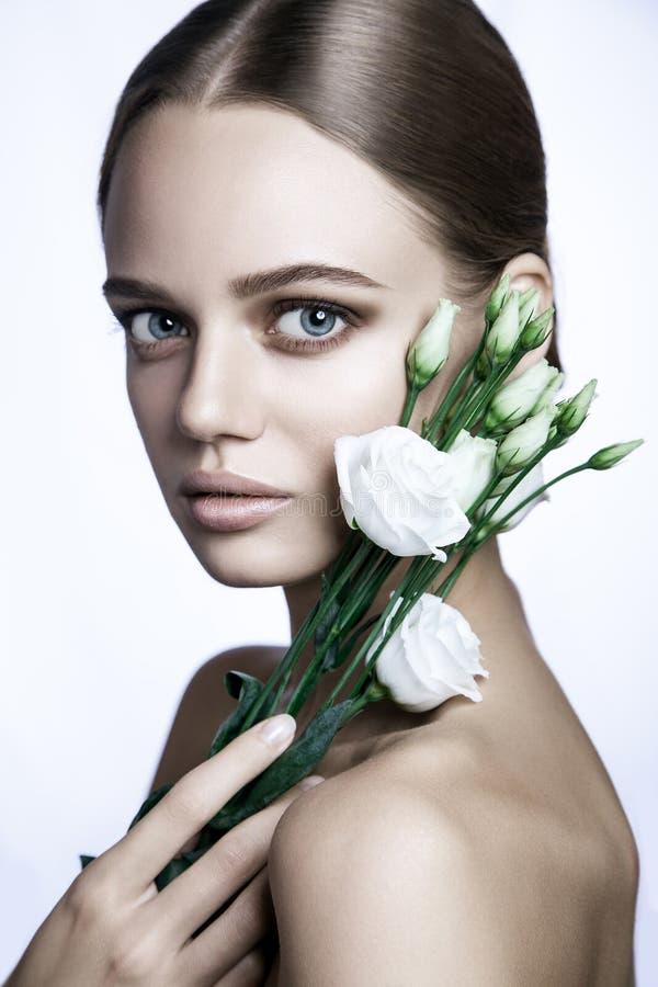 镇静秀丽时装模特儿妇女面孔 与白玫瑰花的画象 免版税库存图片
