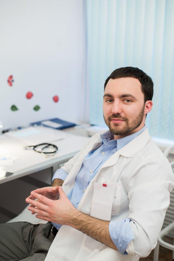 镇静医生或顾问在有他的听诊器的书桌坐看对照相机的桌 免版税库存图片