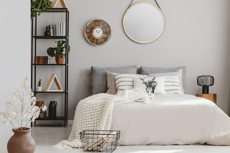 镜子和木时钟在典雅的卧室墙壁上有米黄卧具和白色温暖的毯子的,真正的照片 免版税库存照片