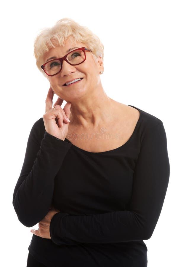 镜片的一个老妇人接触她的面孔。 免版税库存图片