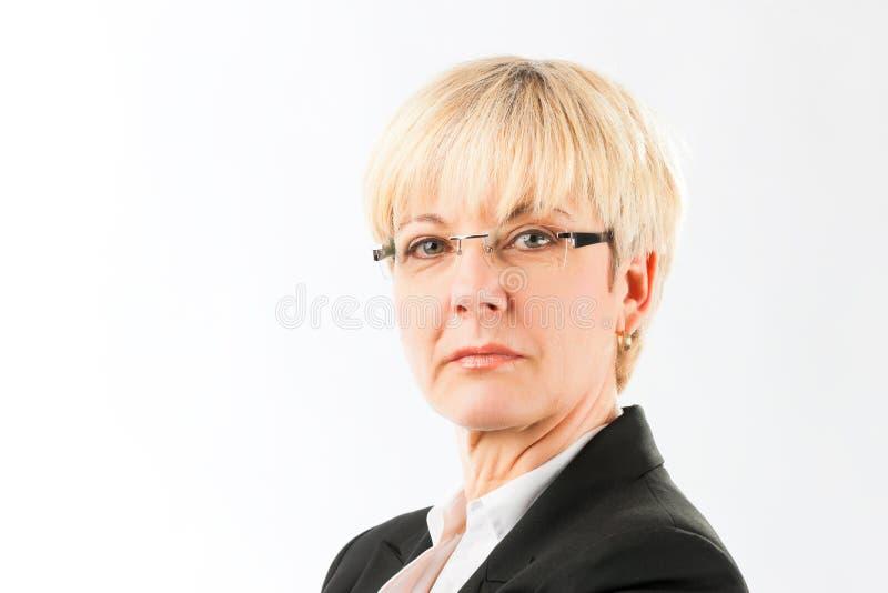 镜片的严肃的资深女商人 免版税库存照片