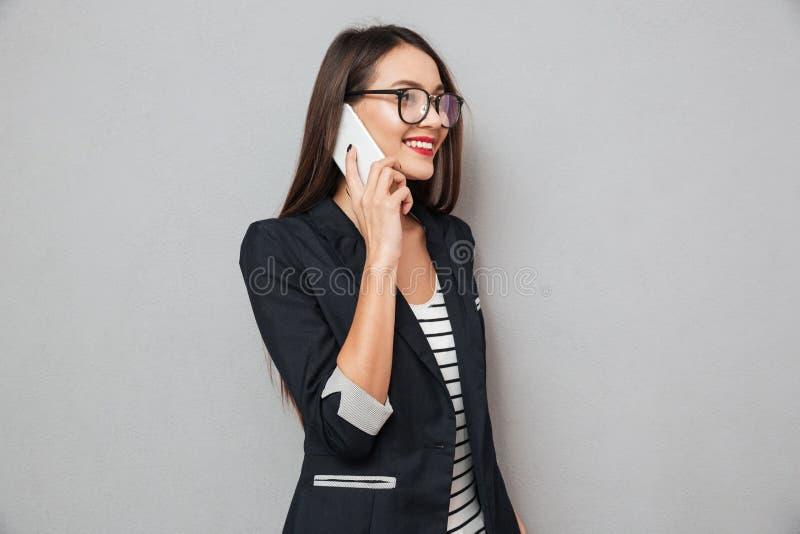 镜片的微笑的亚裔女商人谈话由智能手机 免版税库存图片