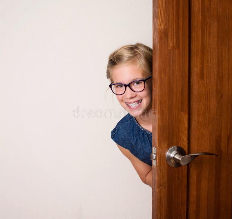镜片的愉快的微笑的逗人喜爱的女孩在门后在家 免版税库存图片