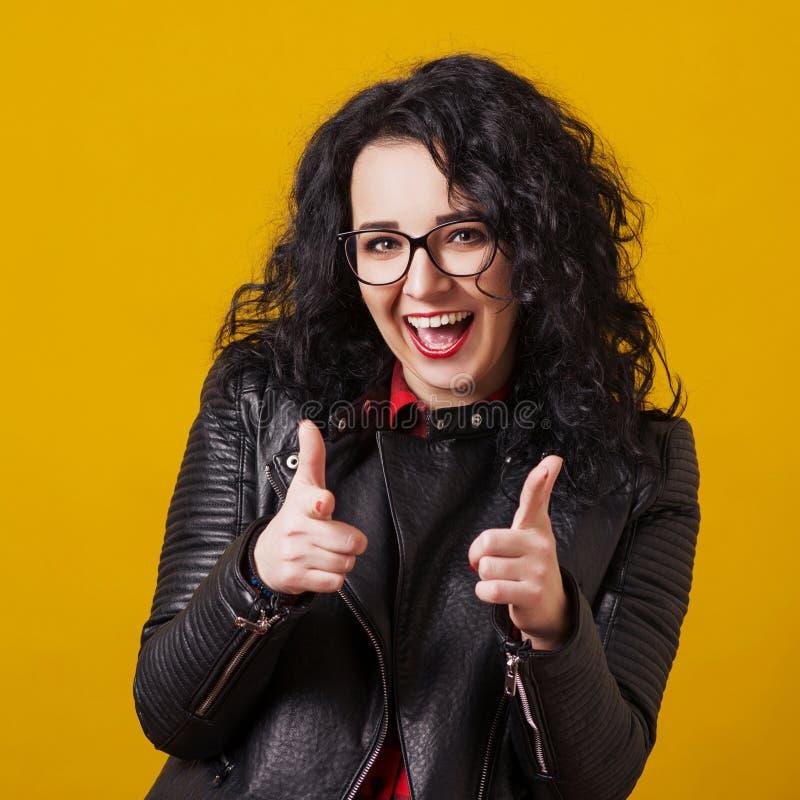 镜片的激动的愉快的妇女 把手指指向的妇女照相机,隔绝在黄色 行家接近的画象玻璃的 免版税库存图片