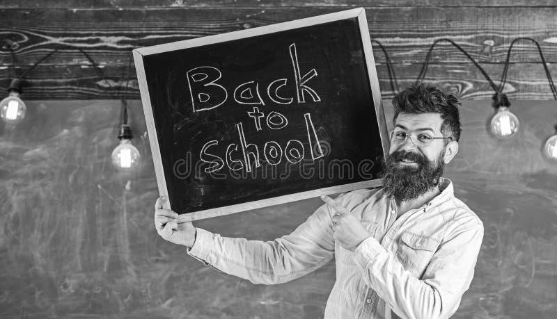 镜片的老师拿着有标题的黑板回到学校 聘用的老师概念 有胡子和髭的人 库存照片