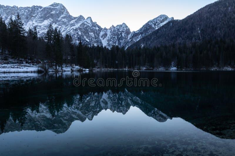 镜象反射山在美丽的fusine湖在朱利安阿尔卑斯在黄昏蓝色小时,意大利 免版税图库摄影