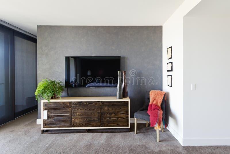 镶嵌墙上的电视和自助餐在宽敞主卧室 免版税库存图片