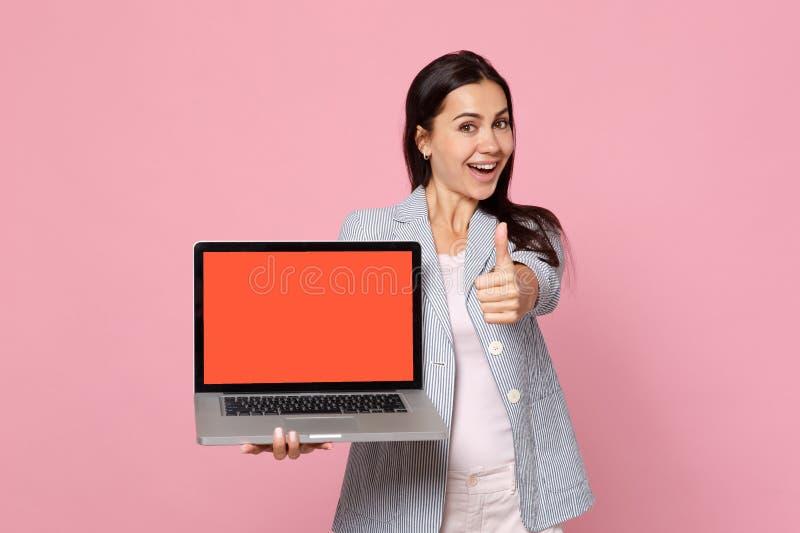 镶边夹克陈列赞许藏品膝上型计算机个人计算机计算机的快乐的妇女有在桃红色隔绝的空白的空的屏幕的 库存照片