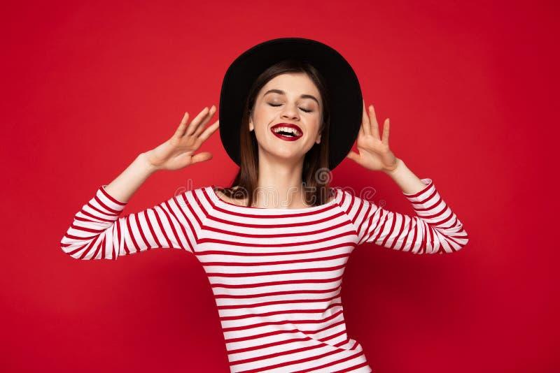 镶边女衬衫和黑帽会议的快乐的夫人 图库摄影