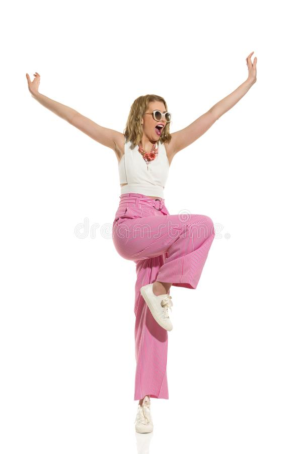 镶边宽腿长裤的愉快的妇女在有胳膊被伸出的和呼喊的一条腿站立 免版税图库摄影