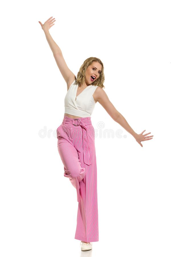 镶边宽腿长裤的无忧无虑的妇女在有被伸出的胳膊的一条腿站立 免版税库存照片