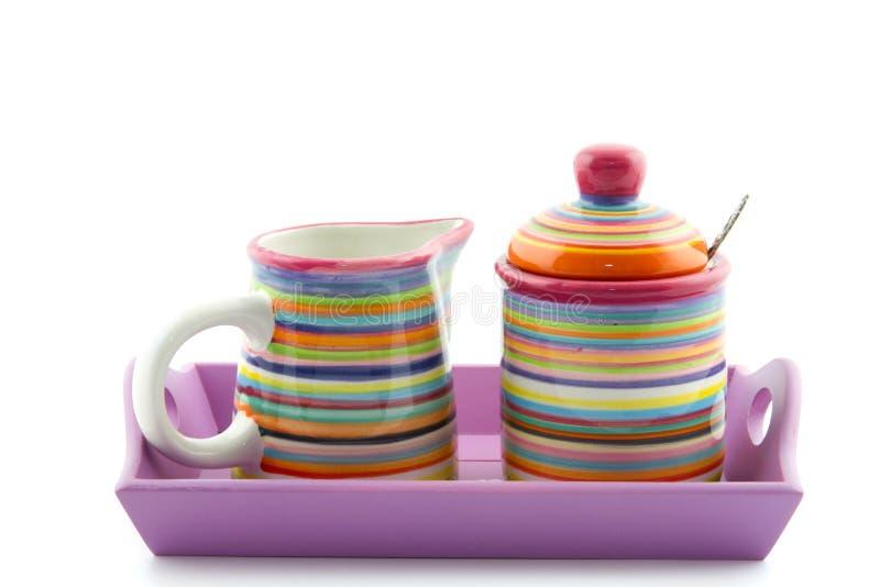 镶边牛奶罐和糖罐在服务盘子 免版税库存图片