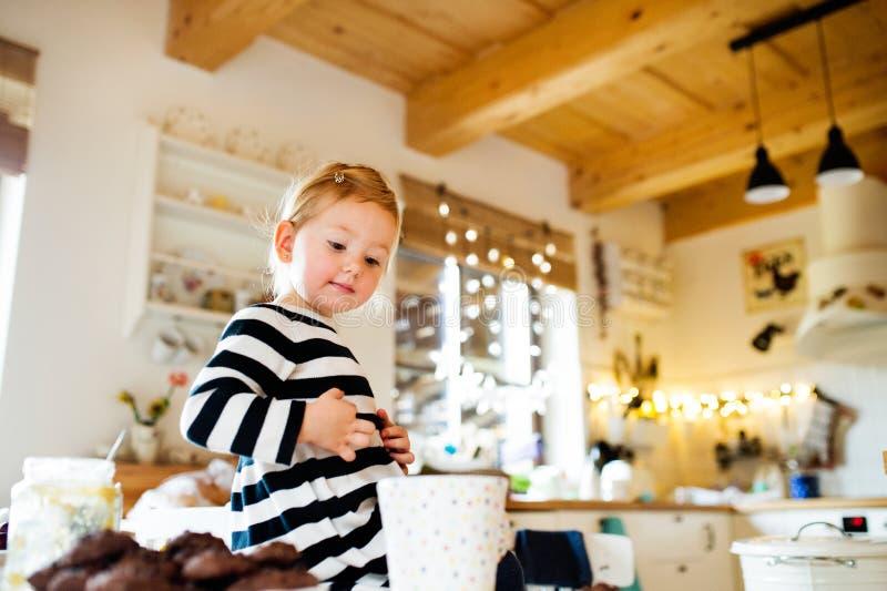 镶边礼服的逗人喜爱的小女孩坐厨房用桌 免版税库存照片