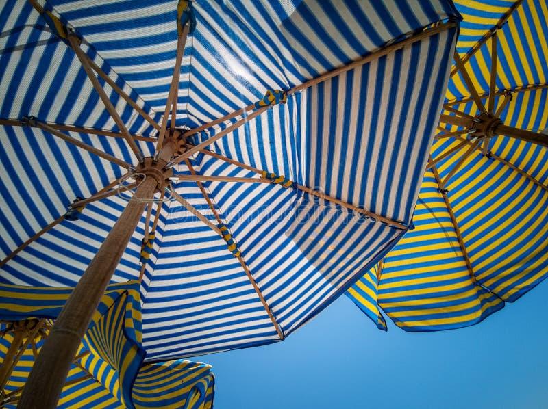 镶边色的沙滩伞背景,从底部的看法,反对天空 免版税库存照片