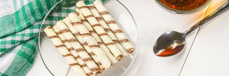镶边薄酥饼在白色木桌滚动,可口巧克力快餐 免版税库存照片