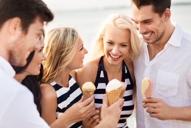 镶边衣裳的愉快的朋友吃冰淇淋的 免版税库存图片