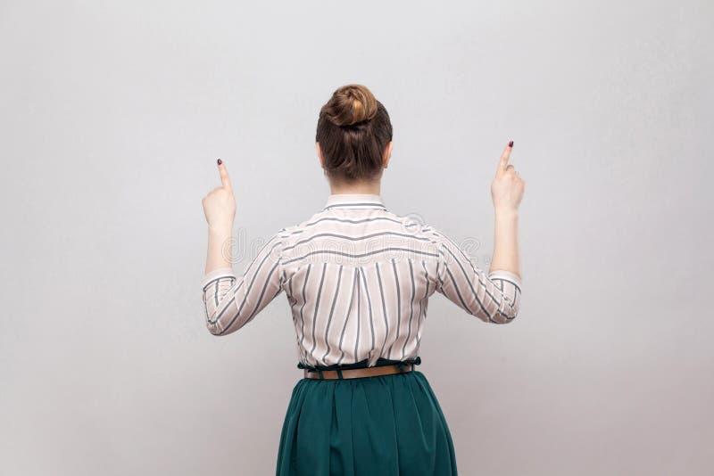 镶边衬衣和绿色裙子的,站立和指向在的美丽的年轻女人和收集的禁令发型后部画象 库存图片