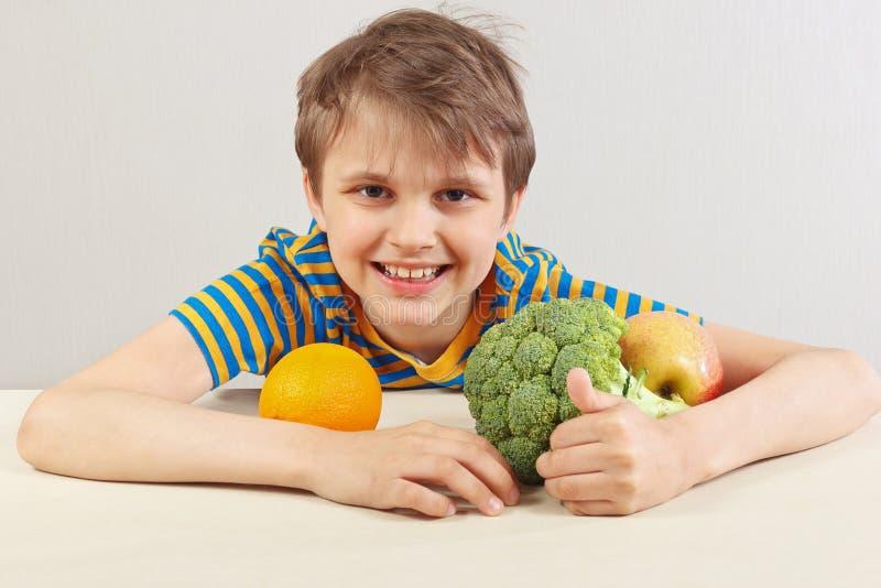 镶边衬衣的年轻滑稽的男孩在桌上用水果和蔬菜在白色背景 库存照片