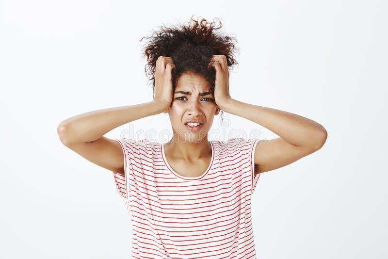 镶边T恤杉的强烈的生气的可爱的妇女,握在头的手,好象紧压它,皱眉从痛苦 免版税库存照片