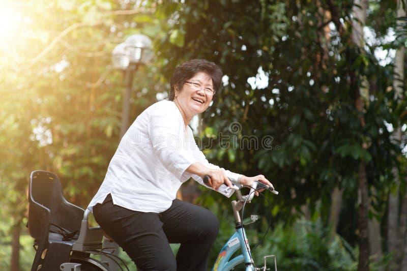 年长亚洲妇女骑自行车 库存照片