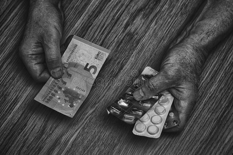 年长人在他的手上拿着药物和金钱 图库摄影