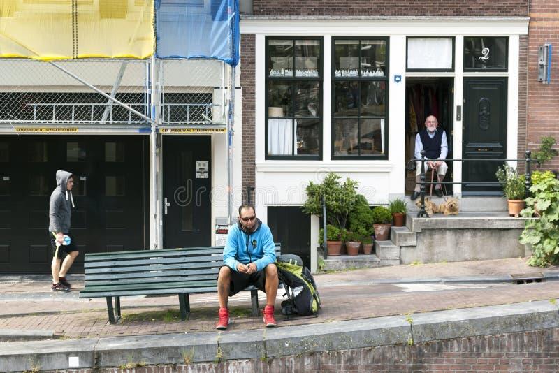 年长人坐与在运河房子门道入口的两条狗amst的 免版税库存照片