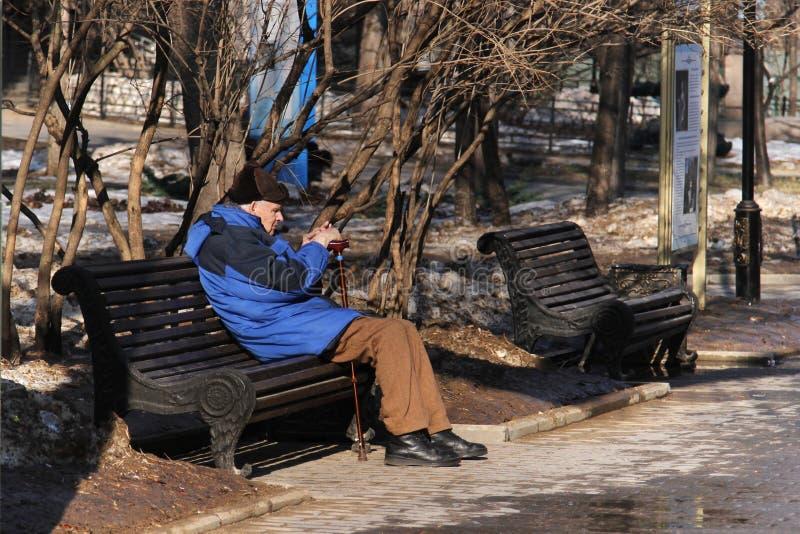 年长人坐长木凳在凯瑟琳公园在一个晴天 库存图片