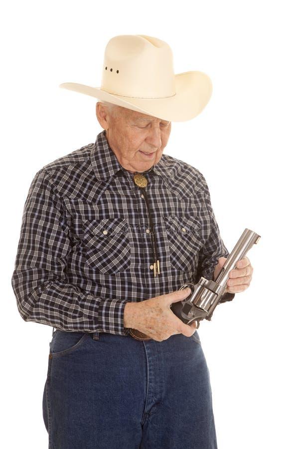 年长人牛仔看看手枪 库存图片