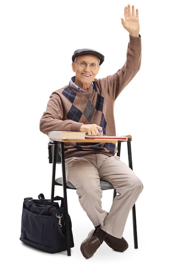 年长人用他的坐直在学校椅子的手 图库摄影
