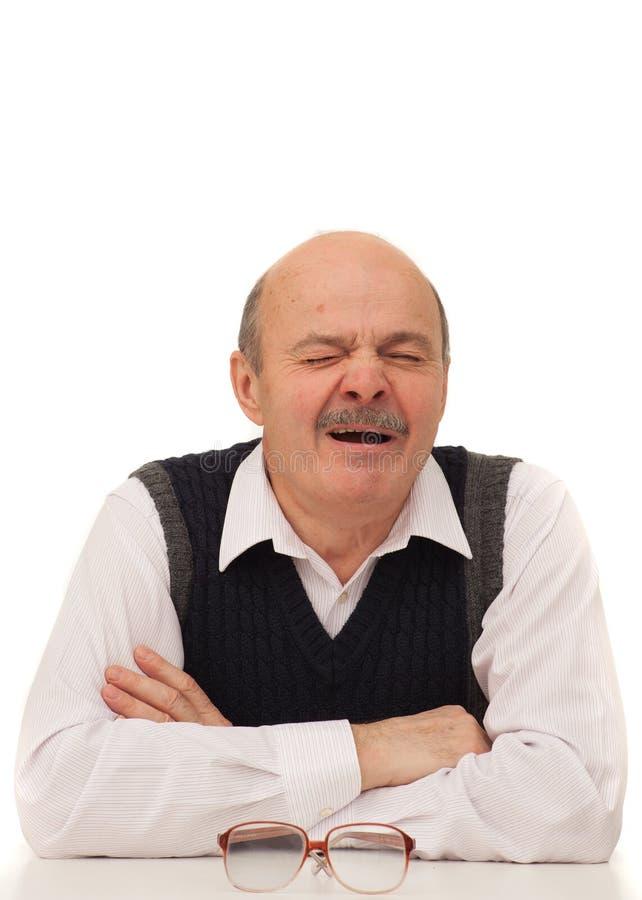 年长人从精疲力尽打呵欠在工作 免版税库存图片