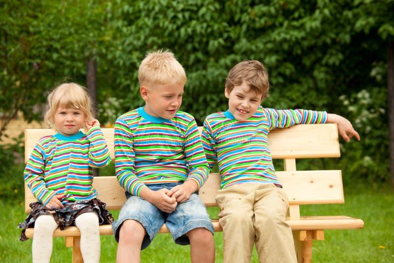 长凳儿童衣裳相同三 库存照片