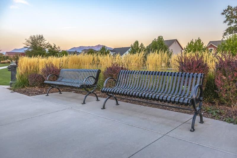 长凳和喷泉反对家和天空 免版税图库摄影