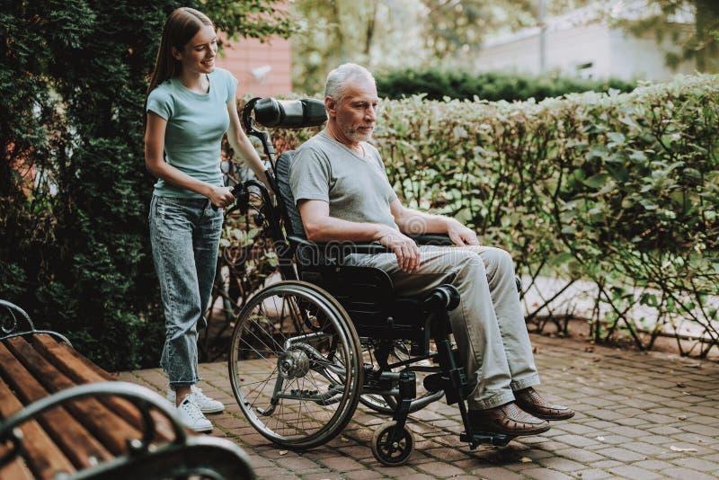 长凳和家庭与老人 有变老的婴儿推车 免版税库存照片