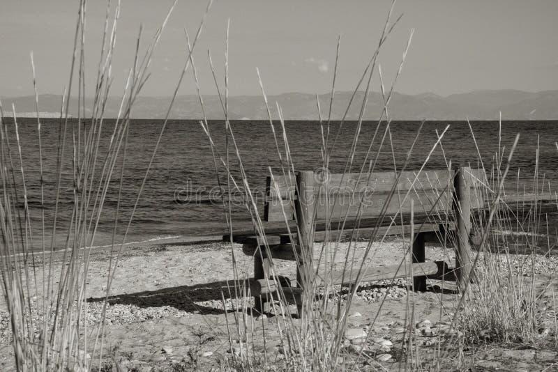 长凳和蓝色海 免版税库存照片
