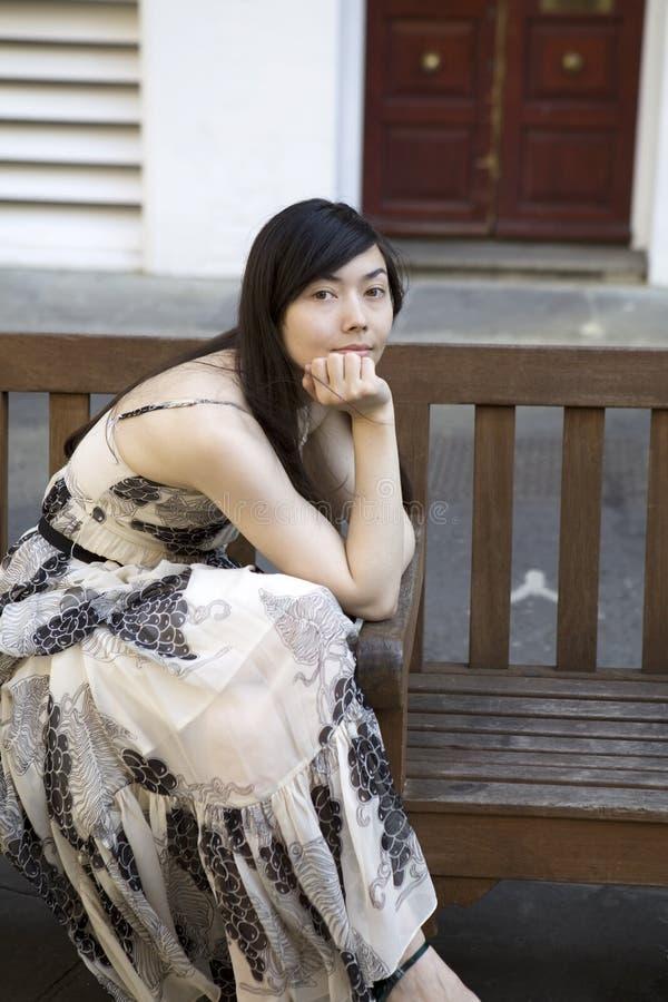 长凳坐的妇女 免版税库存照片