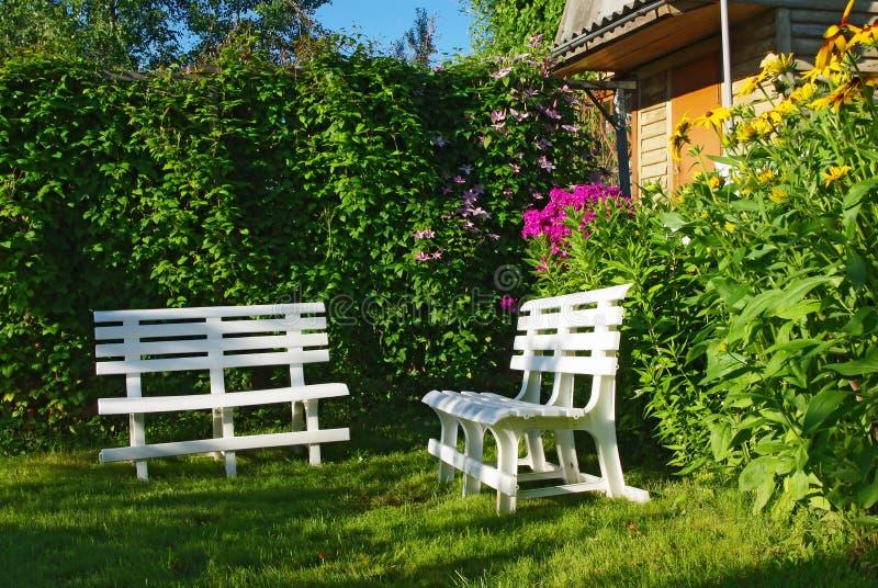 长凳壁角庭院偏僻的白色 免版税库存照片