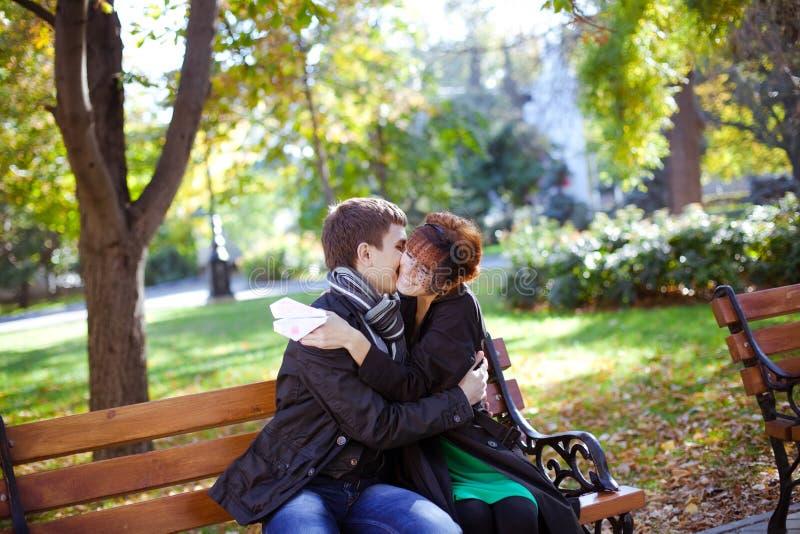 长凳夫妇愉快的公园坐的年轻人 免版税库存图片