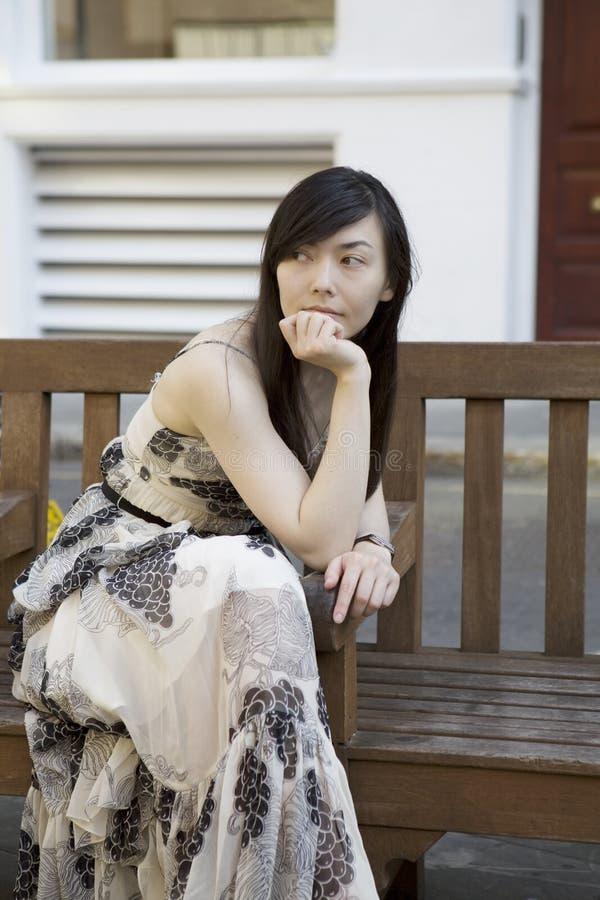 长凳沉思坐的妇女 免版税图库摄影