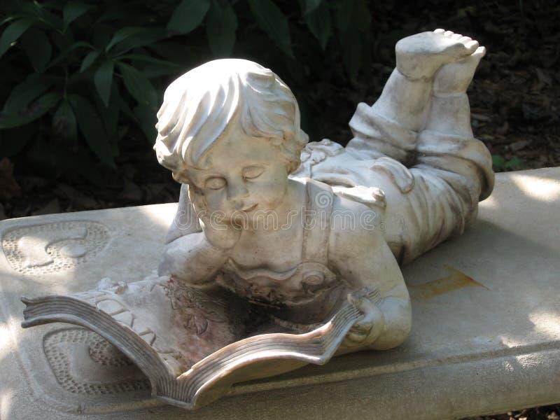 长凳男孩读取雕象 免版税库存照片