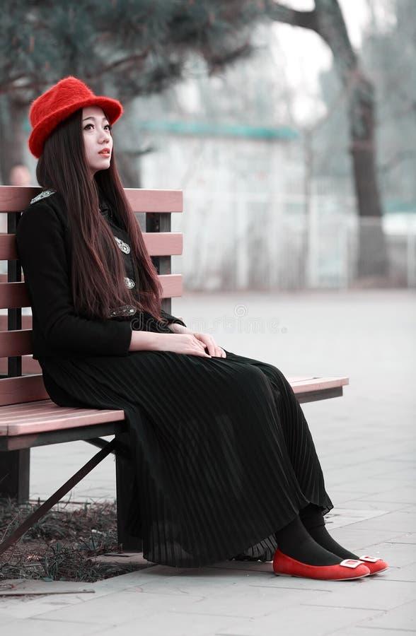 长凳的亚裔女孩 库存照片