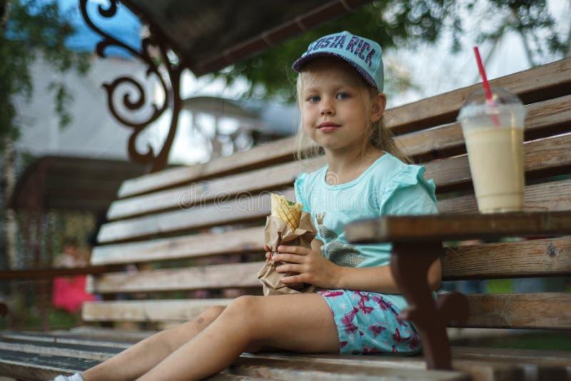 长凳的女孩吃街道食物 免版税库存照片