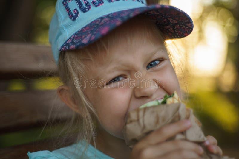 长凳的女孩吃街道食物 库存图片