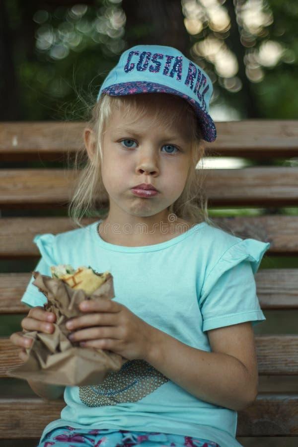 长凳的女孩吃街道食物 图库摄影