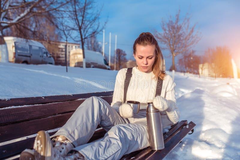 长凳的女孩在总体在街道,背景雪漂泊上的冬天 在一个热水瓶的手上用热的茶咖啡 免版税库存照片