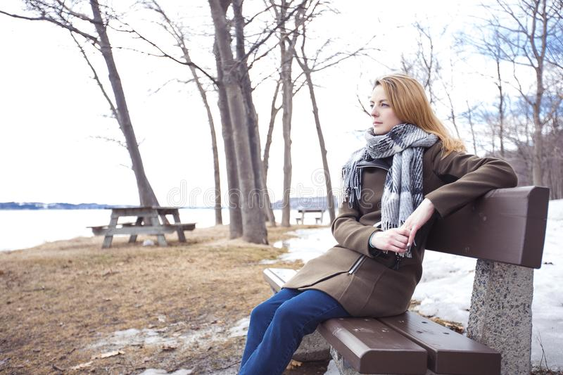 长凳的年轻孤独的妇女在公园 免版税库存照片