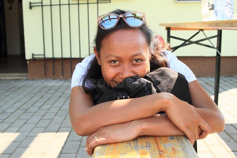 长凳的微笑的热带女孩 库存照片