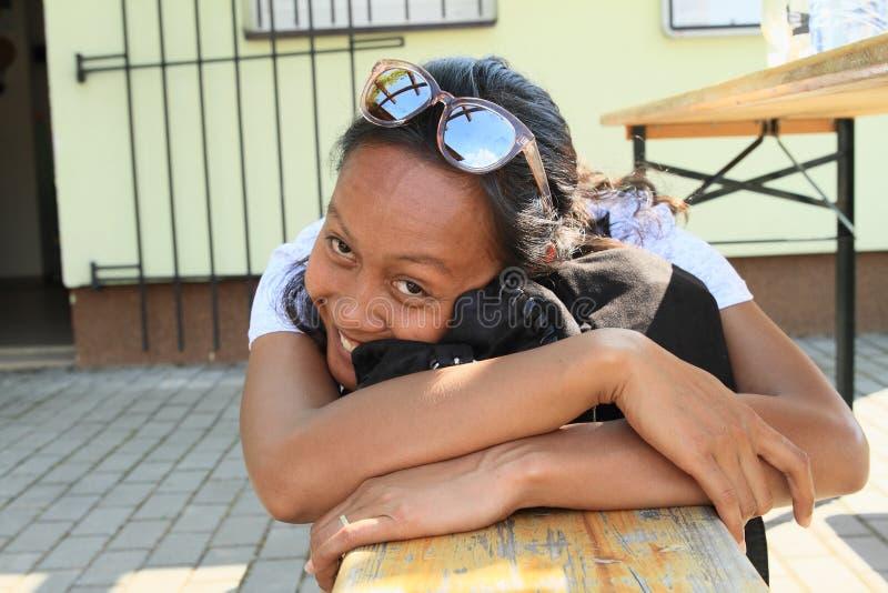 长凳的微笑的热带女孩 免版税库存照片