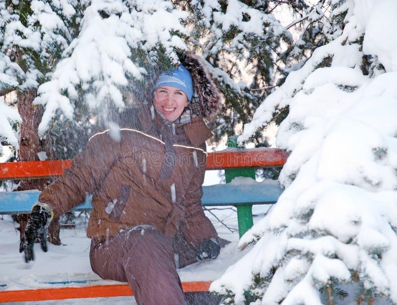 长凳的愉快的女孩在雪 库存照片